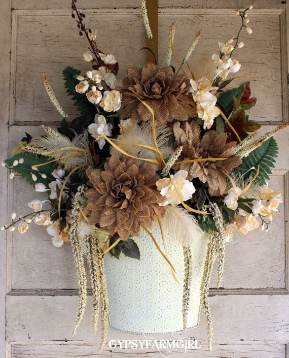 A shabby chic wall pocket to match your vintage home décor. Burlap dahlias, gerbera daisies, and creamy colored delphinium blooms are arranged