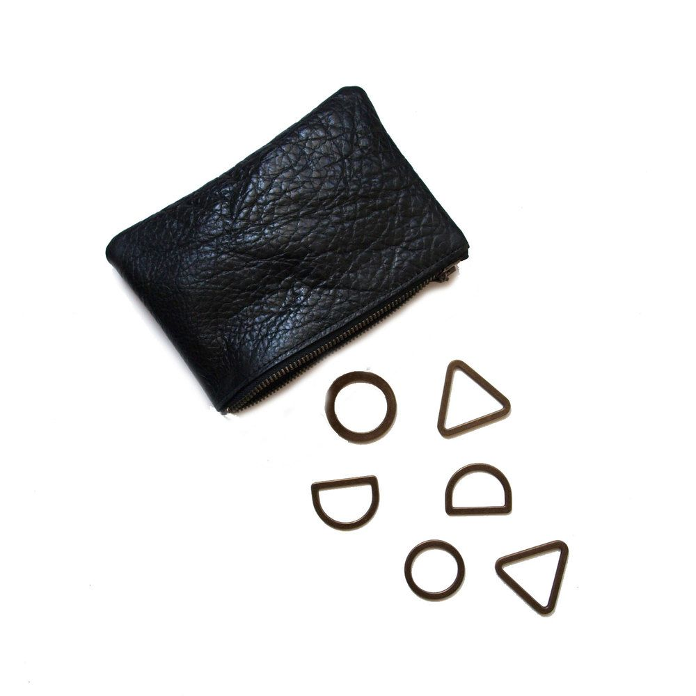 """A charming little pouch sewn from the softest, most textured section of the  leather hide.  The perfect for size for stashing lipstick, headphones, coins, or other  small items.  Measures 6.5 x 4.5"""" Textured black leather. Antique brass zipper. Lined in bright floral  cotton.  * Please note: deep marks and ridges may be present on this small pouch due  to the nature of the leather piece.  Ready to ship."""