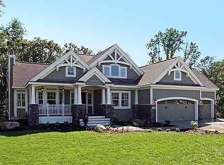 White woodwork at the peaks with white columns and carriage garage doors the exterior home for Exterior house peak decorations