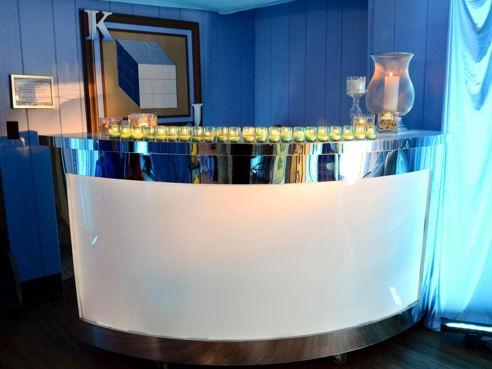 After shot of the bar at Alexis & Kevin Carberry's baby shower party. A curved white bar with mirrored edges on casters is lined with yellow candles and is very easily moved. #design #homebars