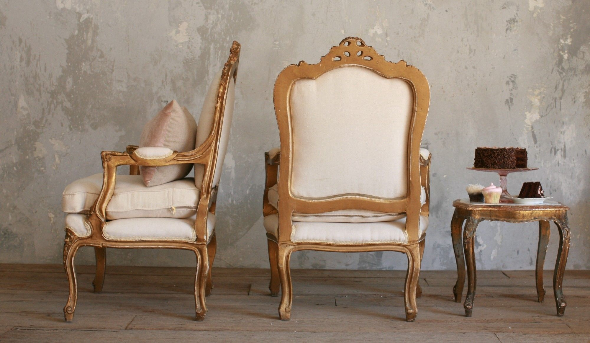 Stunning gold gilded arm chairs with wreath ornamentation at the top, legs, and center bottom. The upholstery is cream canvas.