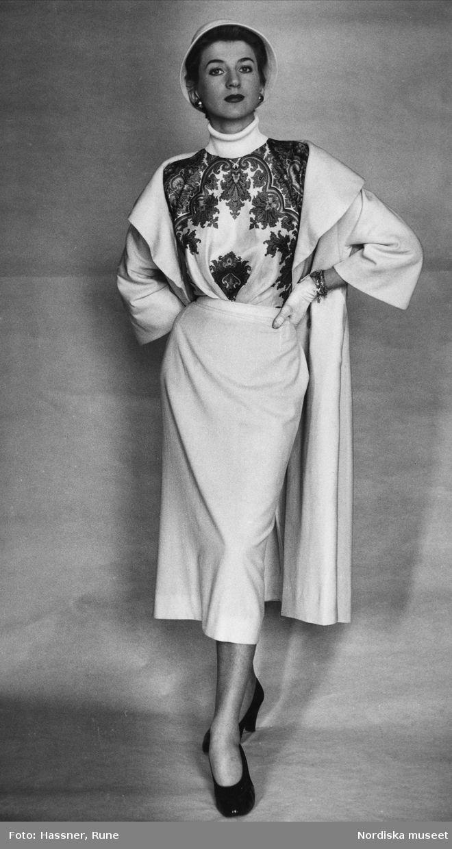 efdc8ed3dee3 Modell klädd i vit kappa, vit vadlång kjol, blus med polokrage, svarta  pumps, vita handskar och vit hatt. Foto: Rune Hassner för Nordiska Kompaniet