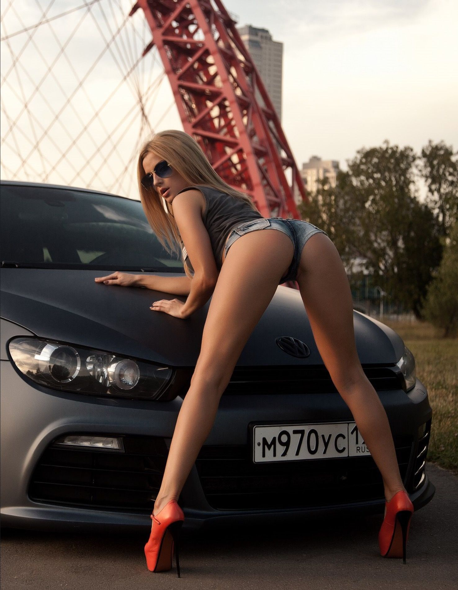 women bending over car