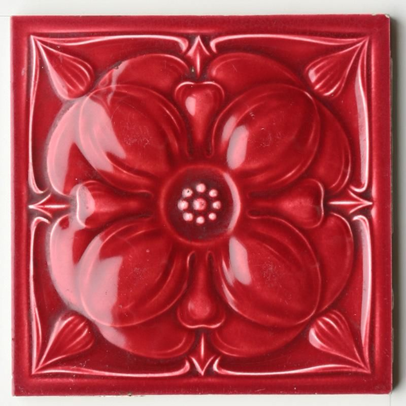An Art Nouveau relief moulded tile in crimson, with a large single flower head and nib corners. Condition: one or...