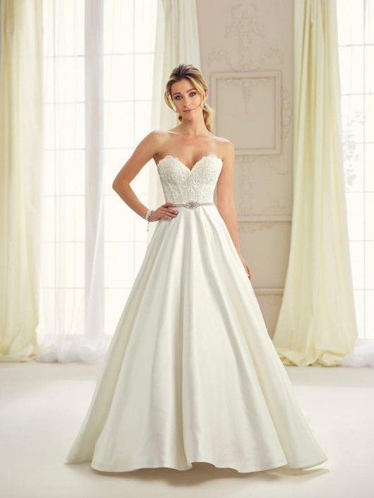 Style 217114 from Enchanting by Mon Cheri is a strapless satin A-line destination wedding gown with a sweetheart neckline, a lace bodice, a beaded waistline, and a chapel length train.
