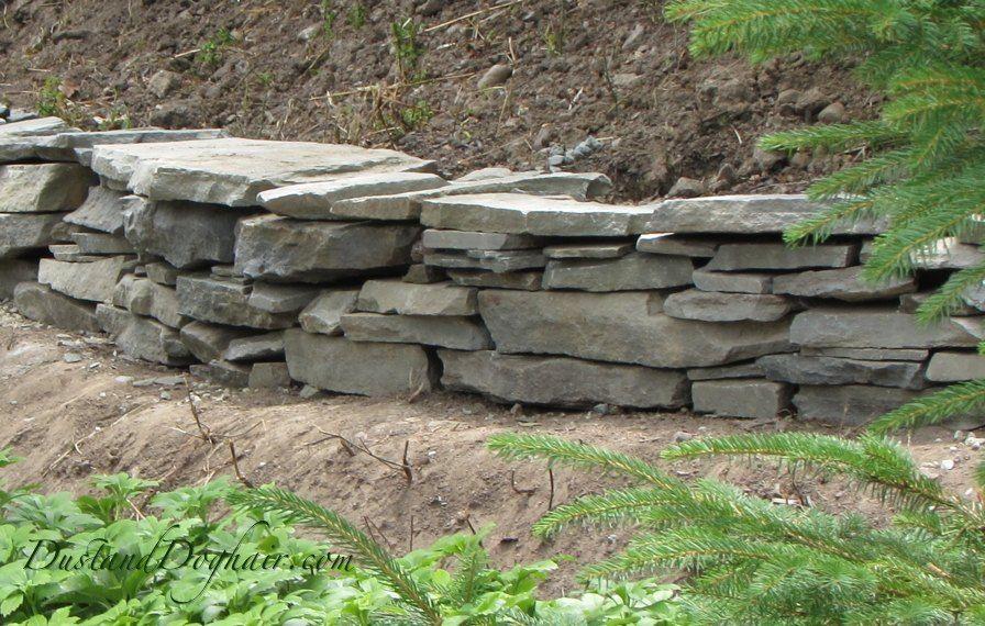 Build A Stacked Stone Garden Wall Garden Stones Garden Wall Stone Retaining Wall