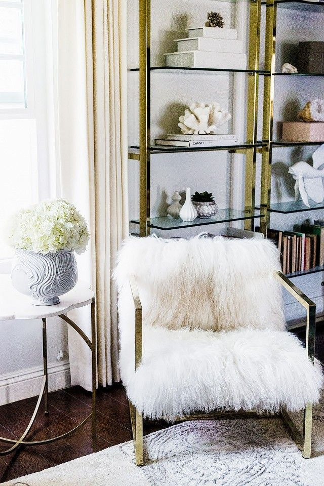 A Chic Living Room Corner With A Fur Armchair And Gold Bookshelves