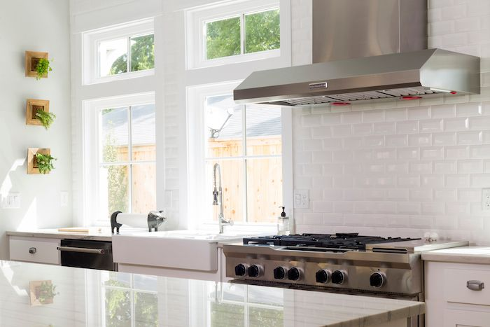 A Classic Yet Modern Kitchen Featuring Beveled White Subway Tile