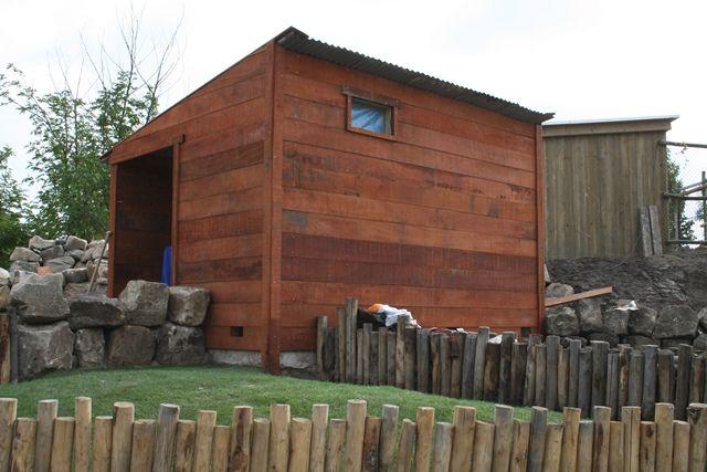 Dierenverblijf van ruwe hardhouten planken en creatieve afrastering van palen.