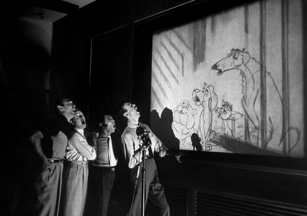 """In a 1953 article titled 'A Silver Anniversary for Walt and Mickey,' LIFE magazine took its readers behind the scenes at Disney. Caption from LIFE. Quartet known as The Mello-Men bays in harmony before screen showing four canine characters whose voices they represent in the forthcoming Disney feature cartoon, """"The Lady and The Tramp."""""""