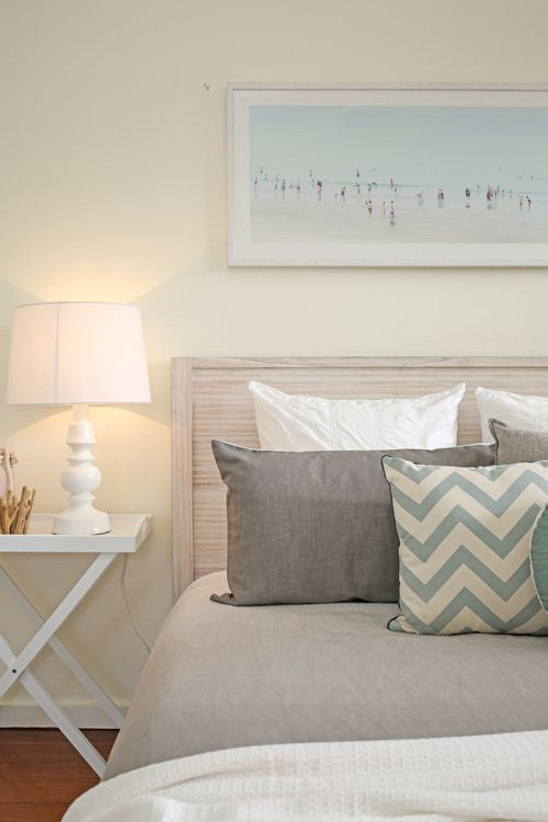 Shabby chic, coastal, beach style, Hamptons, guest bedroom, master bedroom, white washed timber bed frame, white tray tables, beach artwork, chevron cushion, round cushion, grey ombre linen