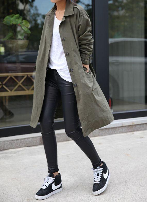dunkelgrüner Trenchcoat, weißes T-Shirt mit einem Rundhalsausschnitt, schwarze Lederleggings, schwarze und weiße niedrige Sneakers für Damen