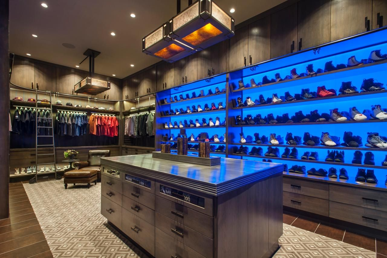 This Massive Walk In Closet Boasts Deep Masculine Tones And Textures Bright Blue LED Panels Turn An Extensive Shoe Collection Into Artful Display While