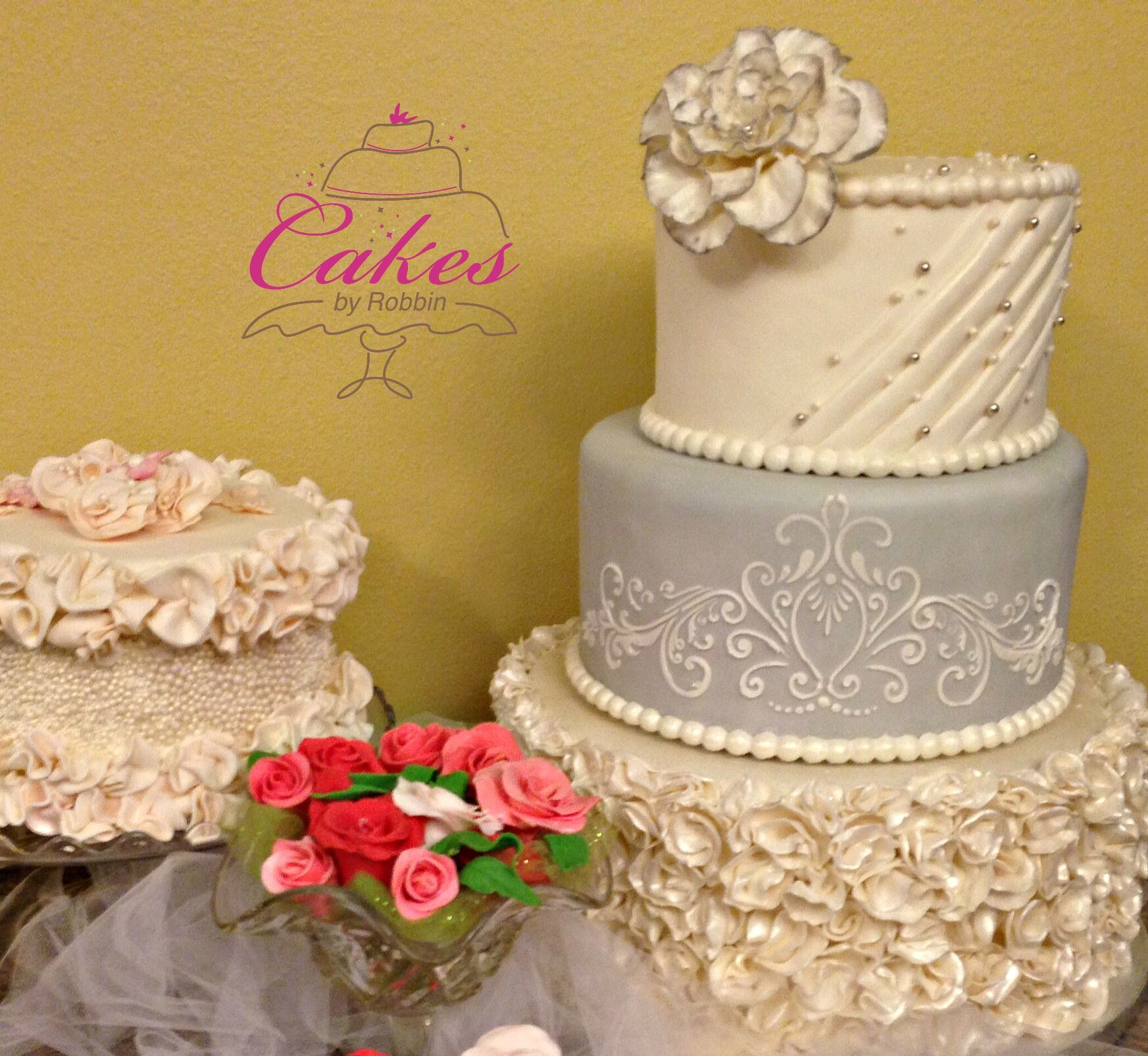 This is a classic grey and white wedding cake with ruffles ...