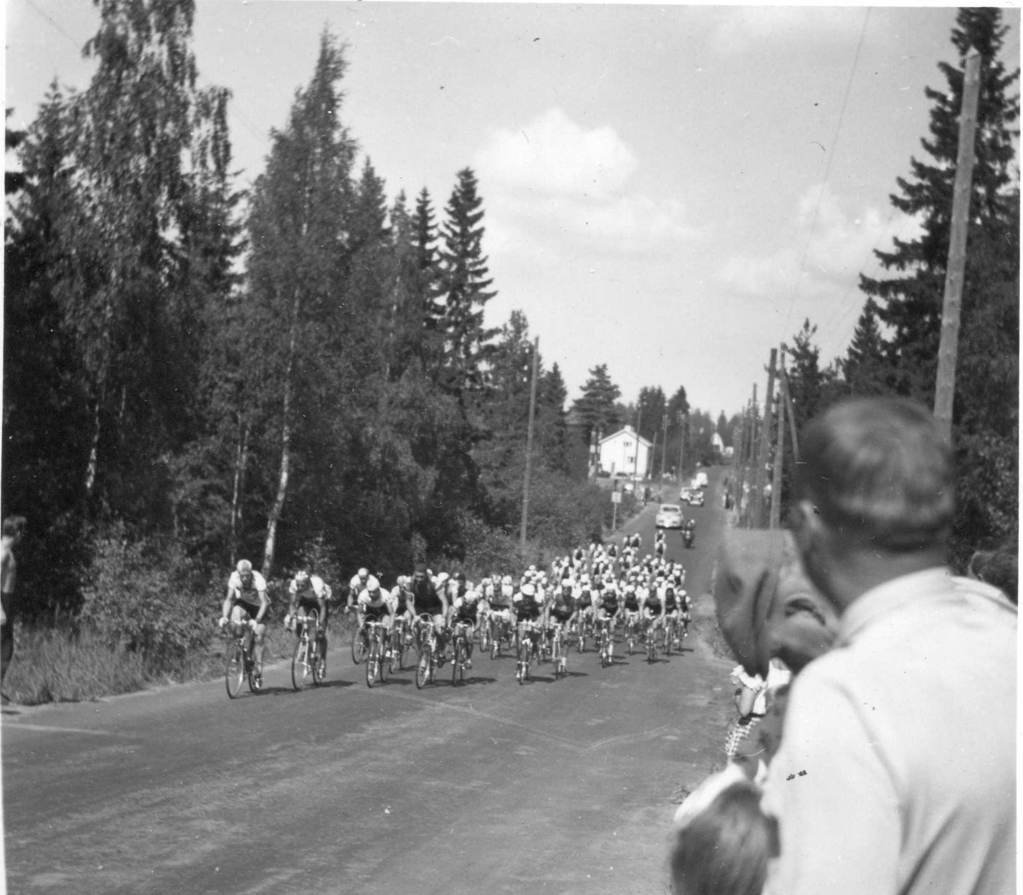 Helsingin olympiakisat 1952, maantiepyöräily, ryhmä menossa Pakilantiellä, nykyisen Kehä I:n pohjoisreunalla, suuntana etelä. Alkuperäinen kuva, Valto Mattila.  Olympialaisten kilpapyöräily,1952