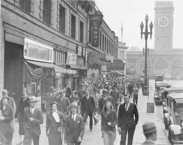 "This is a photograph of people walking along Market Street in San Francisco, California the week after ""Bloody Thursday."" Bloody Thursday was the climax of the 1934 West Coast Longshoremen's Strike. The strike last 83 days, with two strikers killed by bullets, another by injuries, 31 others were shot and an untold number, including police, were clubbed, gassed and beaten."