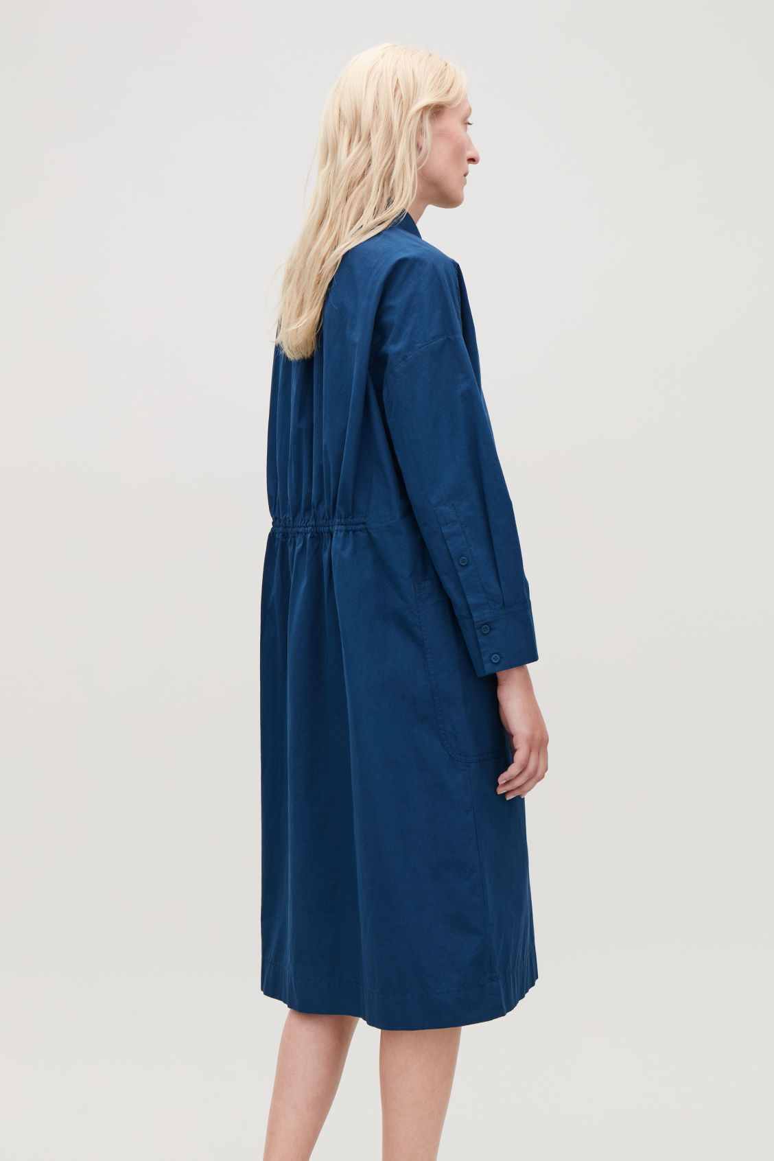 f3aa796ea20 Model side image of Cos long jacket with gathered back in blue Cuff  Sleeves
