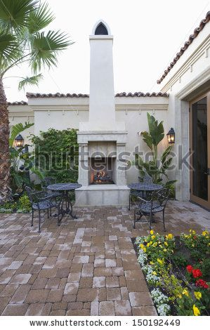 Chairs and tables at outdoor fireplace in courtyard garden of home by bikeriderlondon, via ShutterStock
