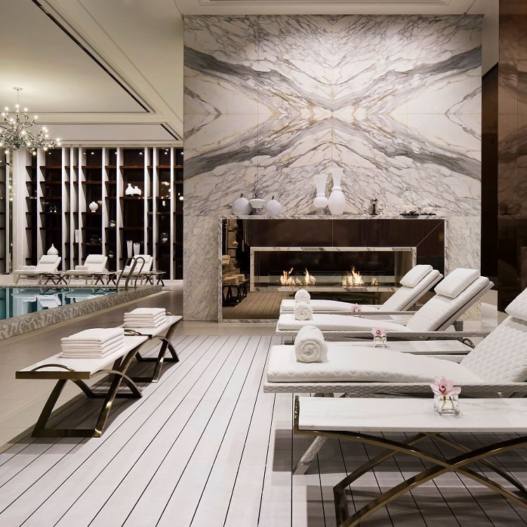 contemporary luxury spa with poolside lounge chairs and marble