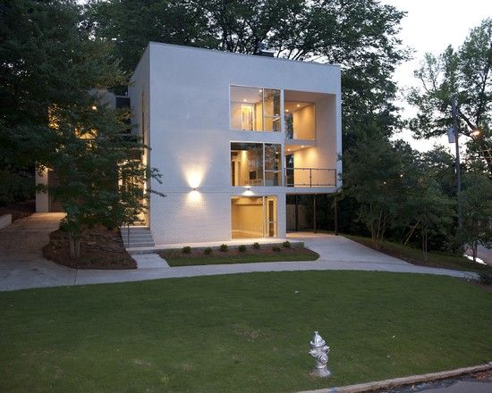 White Small Cube House Design With Carport Under The Corner Of The House  With Glass
