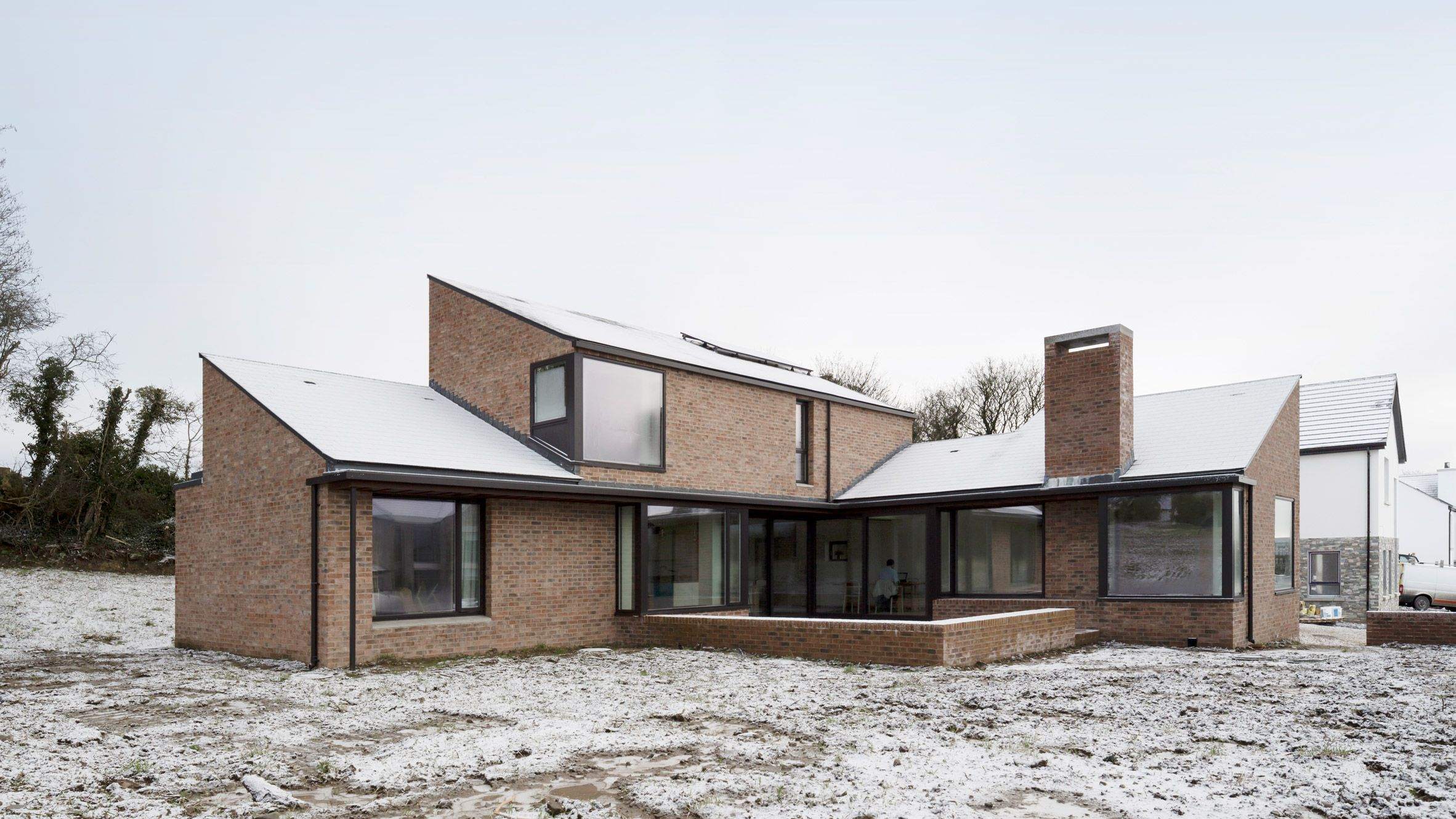 Scullion Architects Has Built An L Shaped Brick House With Sloping Roofs On The Outskirts Of A Seaside Village Near Modern Brick House Brick Architecture House
