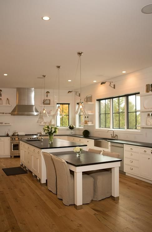 Two Glass Cone Shaped Pendants Hang Over A White Kitchen Island Topped With Soapstone Fitted With A P Kitchen Island Design Kitchen Design Kitchen Island Table