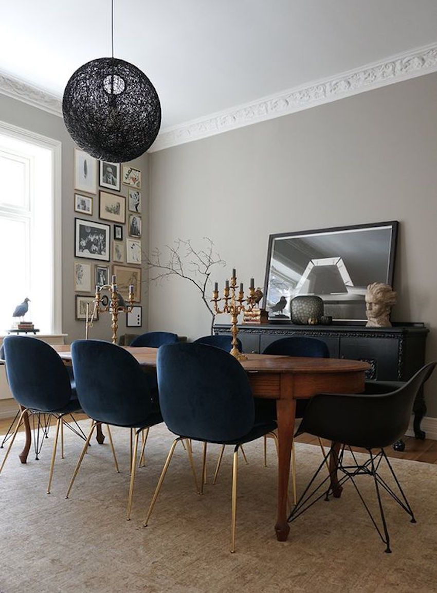 Chic eclectic dining room with lovely grey walls blue velvet upholstered chairs and a wood oval dining table an ornate nest for three in norway