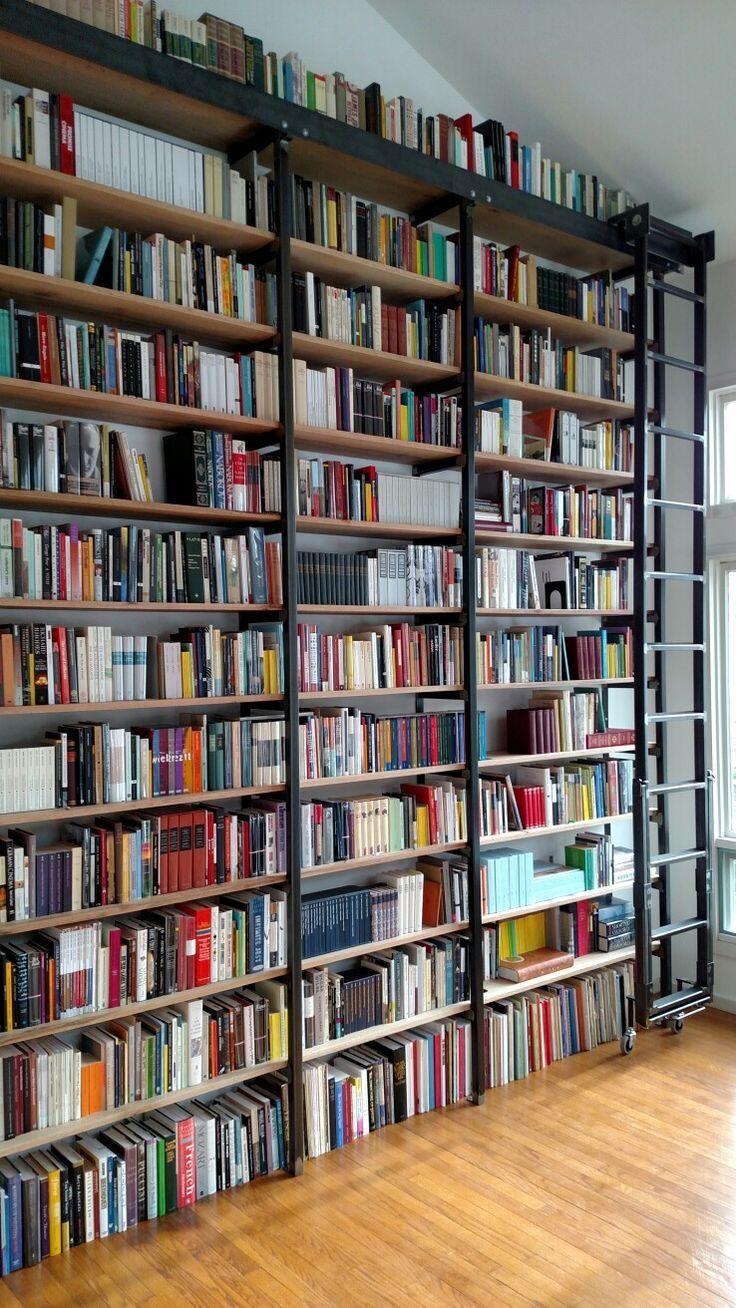 Custom made iron library bookshelf with rolling ladder from wall to