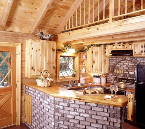 Log Home Kitchen With Brick Counter And Wall Behind Stove