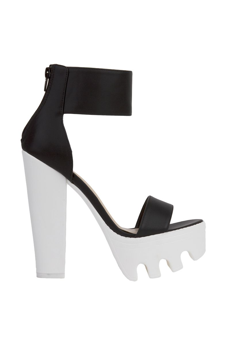 The Open Toe Lug Sole Platform Black White Heeled Sandals features an open toe, an ankle strap, chunky heel, lugged platform, and a back zip closure. Free standard U.S. shipping $75+.