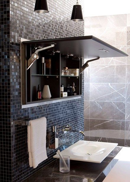 At first glance, it seems this space lacks storage. A closer inspection of the mirror above the vanity reveals otherwise, for the panel opens up to expose hidden shelves recessed into the tiled wall. This clever design trick frees up space, and provides a handy nook for storing toothbrushes and other toiletries.