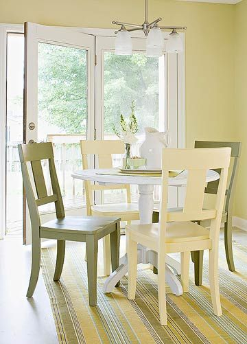 A Simple White Dining Table Offers A Cottagelike Feel. Yellow And Green Dining  Chairs Add