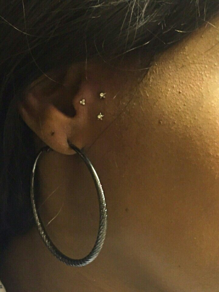 Vertical and tragus piercing. Surface stars.