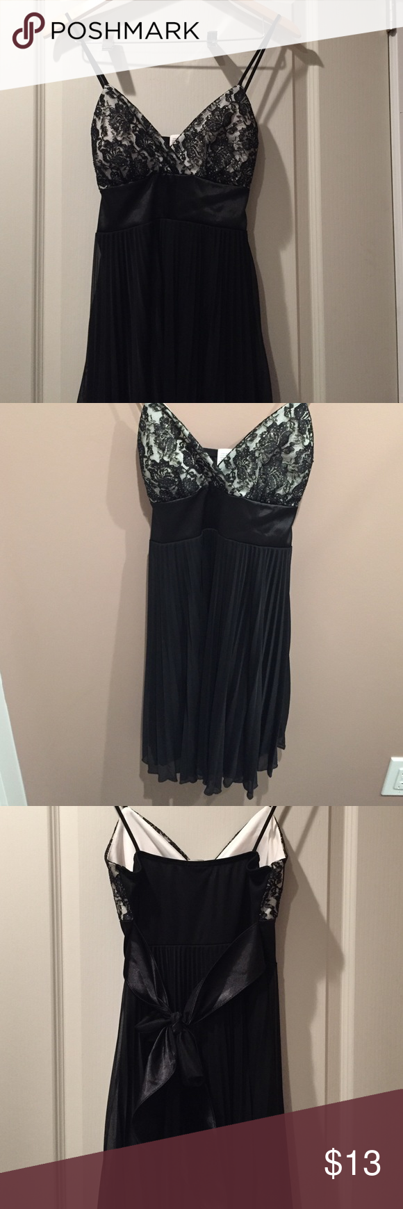 Little black dress with bow tie back Dress was worn once, has a bow tie back and chiffon overlay. Top is V drop with black lace floral design and spaghetti strap, fits true to a medium and top provides good coverage for B to A cup Dresses Midi