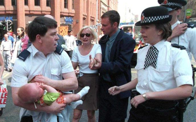 Seven month old Sam Hughes is held by a security guard following the 1996 IRA Manchester bombing. Read more at http://www.telegraph.co.uk/men/the-filter/next-mark-zuckerberg-meet-sam-hughes-ira-bomb-survivor-tech/?WT.mc_id=tmg_share_fb