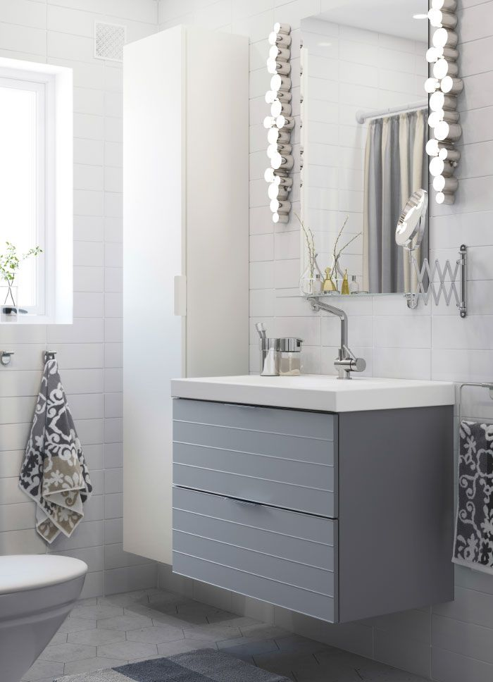 A White Small Bathroom With A White High Cabinet A Mirror And A