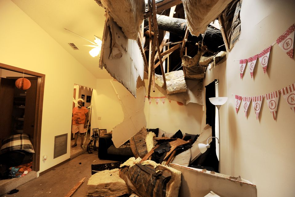 STORM DAMAGE: Sandra Beaver looked into the living room of her Ft. Caroline Lakes home in Jacksonville, Fla., after a tree came through the roof during a storm Thursday. (Bob Self/The Florida Times-Union/Associated Press)