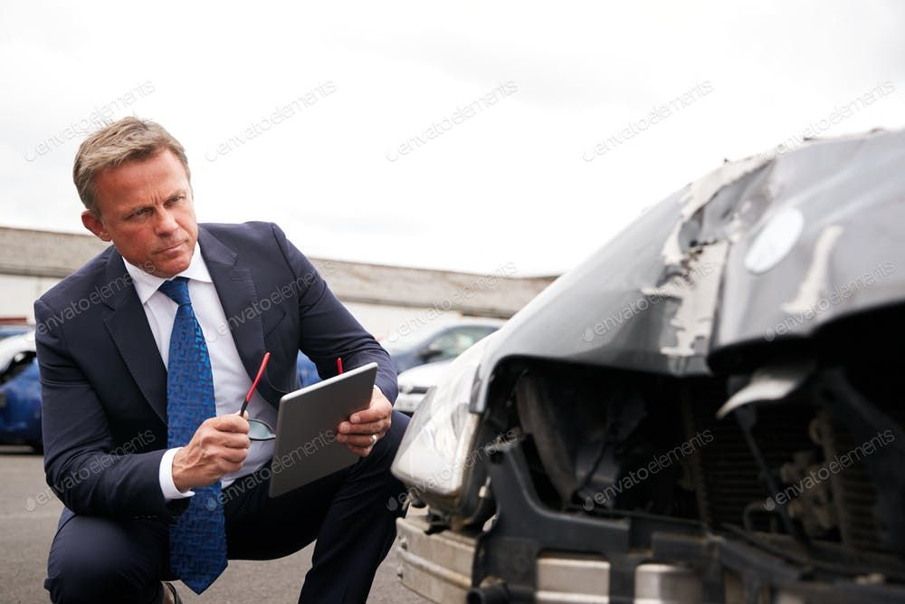 Male Insurance Loss Adjuster With Digital Tablet Inspecting Damage