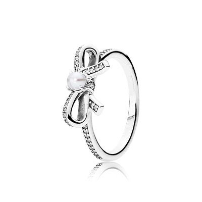 Elegant and chic, this refined silver ring features a feminine bow adorned with a luminous white cultured pearl. Delicate rings are a major trend and beg to be stacked together for statement-making style. #PANDORA #PANDORAring