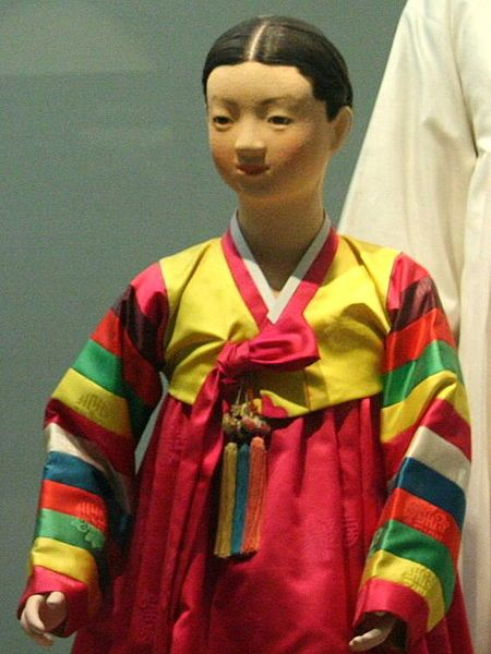 """Saekdongot is any hanbok patchworked with colorful stripes. It began to be made since the Goryeo period (918 – 1392). The name literally means """"many colored clothing"""". It was usually worn by children of the age at one to seven year old. The saekdong can be applied throughout jeogori (short jacket with sash), majoja (buttoned jacket), durumagi (overcoat) or among others."""