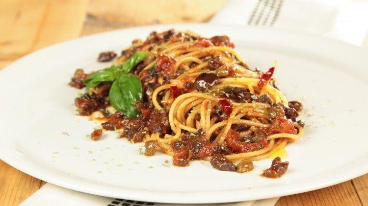 Ricetta Spaghetti in salsa eoliana: Dissalate, innanzitutto, i capperi e tritateli grossolanamente con le olive. Scaldate in una padella l'olio con lo spicchio d'aglio e, quando ben caldo, saltatevi il trito di olive e capperi. Aggiungete i pomodori pelati e lasciate cuocere il