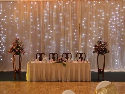 Simple Back Lit Drape In Wedding Colours With Free Standing Flowers On Either End