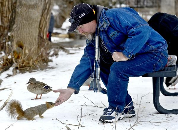 """A man who gave his name as """"Kentucky John"""" hangs out on a park bench feeding a squirrel and duck while waiting to go back to the Boulder Shelter for the Homeless on Tuesday"""