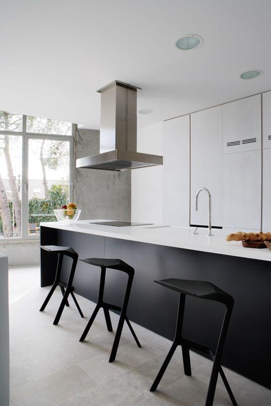 Cuisine minimaliste en blanc et noir - j'aime le contraste des meubles blancs côté cuisine et du noir côté bar (y compris les tabourets design):
