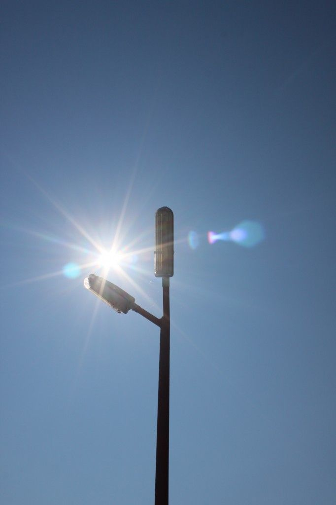 Sun Shining And Street Light Poles Against Blue Sky Public