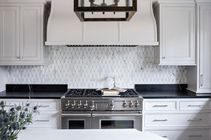 Chic kitchen boasts pure white cabinets paired with soapstone ... on