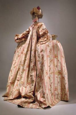 The remarkable characteristic of ROBE A LA FRANCAISE OR SACK BACK are the highly structured box pleats, which are attached to the neck of the bodice and flow delicately down the back of the gown into a short train. This style was often decorated lavishly with puffs, bows, lace, ribbons, cording, etc.