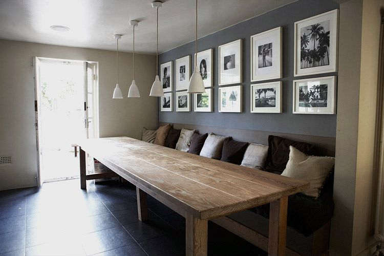 Large Dining Table With A Built In Bench And Wall Behind Decorated Pics