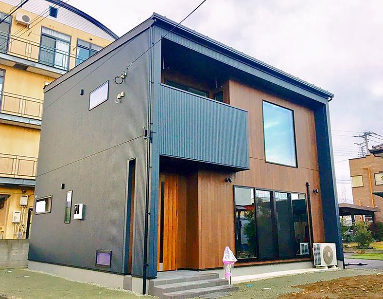 ブラックの外壁をベースに アクセントには木目調の外壁と玄関ドアを