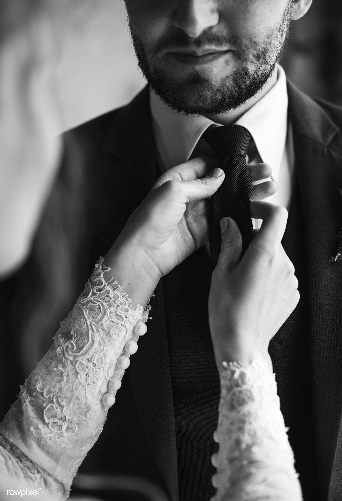 Download premium photo of Bride Helping Groom Dressing Up